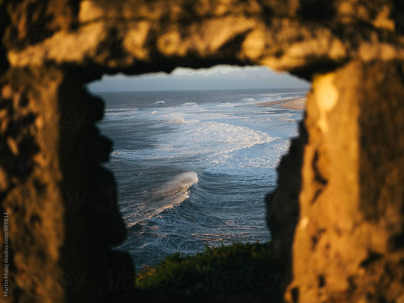 Waves in the ocean framed inside fortress window by Martin Matej for Stocksy United