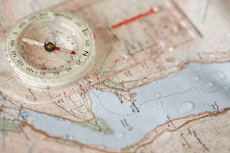 Rain droplets on a waterproof map and compass. by Liam Grant for Stocksy United