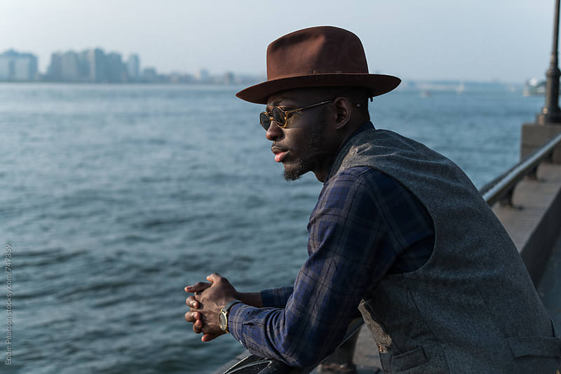 Stylish man overlooking Manhattan water by Eddie Pearson for Stocksy United