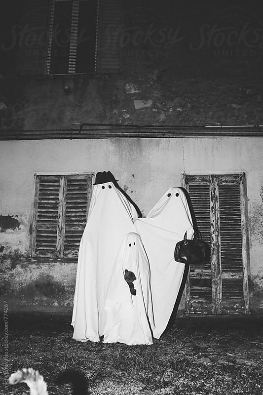 Family of ghosts in front of their home in black and white by michela ravasio for Stocksy United
