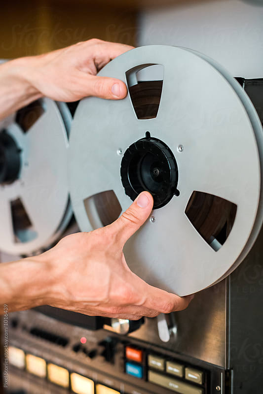 Person placing reel on recorded by Pixel Stories for Stocksy United