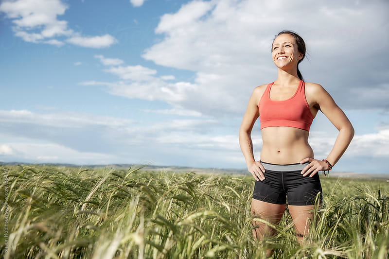 A smiling fit woman standing in a wheat field in workout clothes by Shaun Robinson for Stocksy United