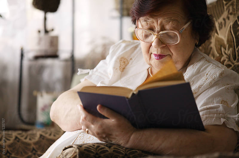 Senior woman reading a book by Ilya for Stocksy United
