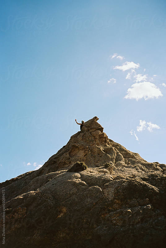 Man climbing the high rock on the island. by Nina Zivkovic for Stocksy United