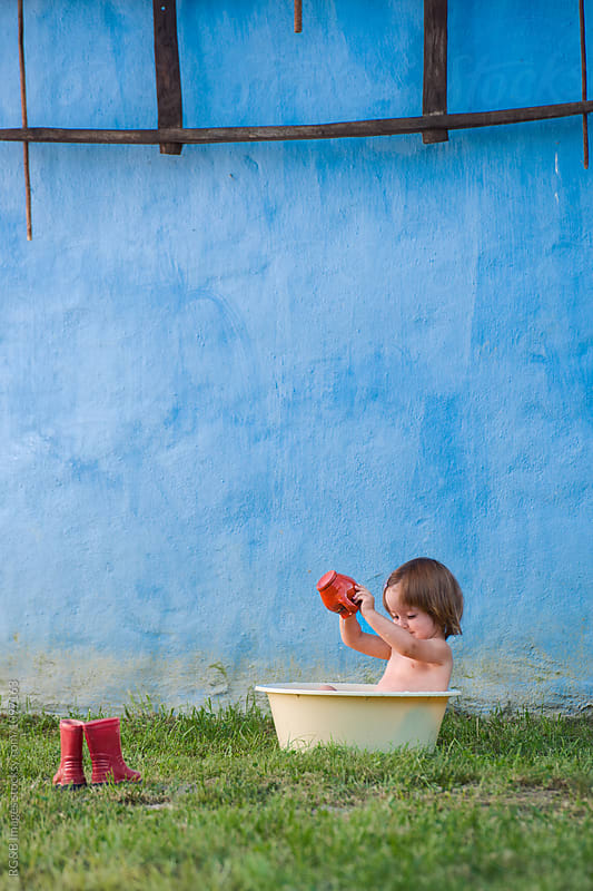 Little girl playing with water while bathing in a plastic basin  by RG&B Images for Stocksy United
