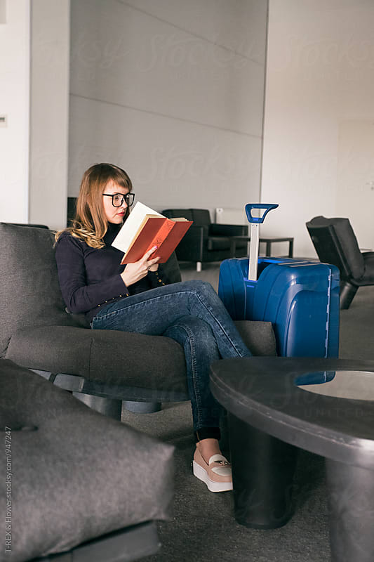 Relaxed woman reading book in business class by Danil Nevsky for Stocksy United
