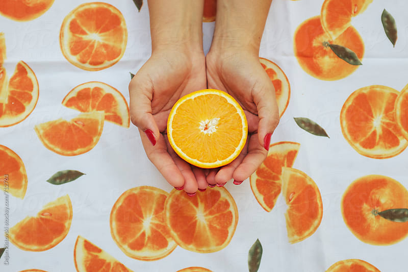 Hands holding half orange by Dejan Ristovski for Stocksy United
