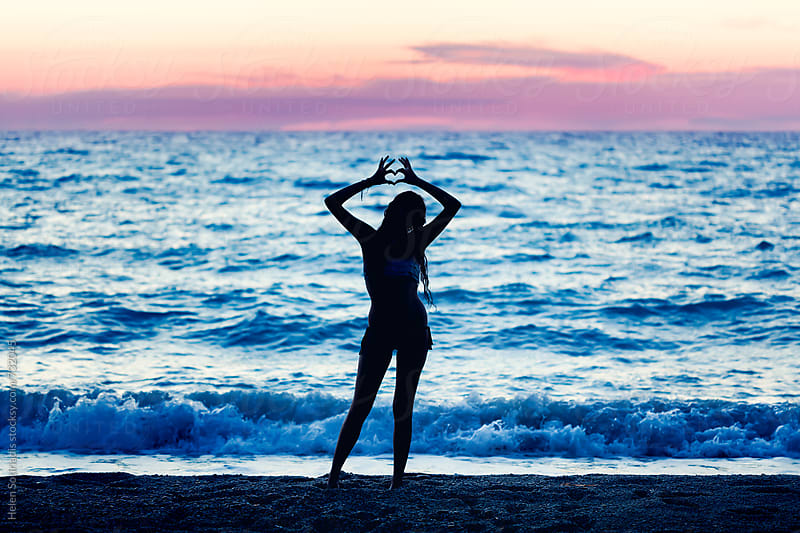 Young Woman Makes a Heart Gesture on the Beach at Twilight by Helen Sotiriadis for Stocksy United