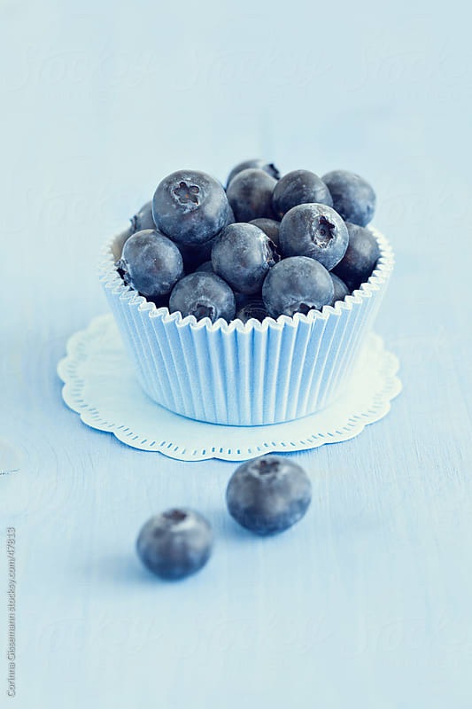 ripe blueberries in a tin on blue background by Corinna Gissemann for Stocksy United
