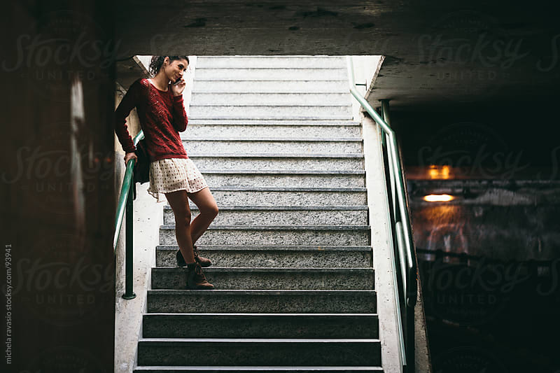 Young woman phoning in an underpass by michela ravasio for Stocksy United