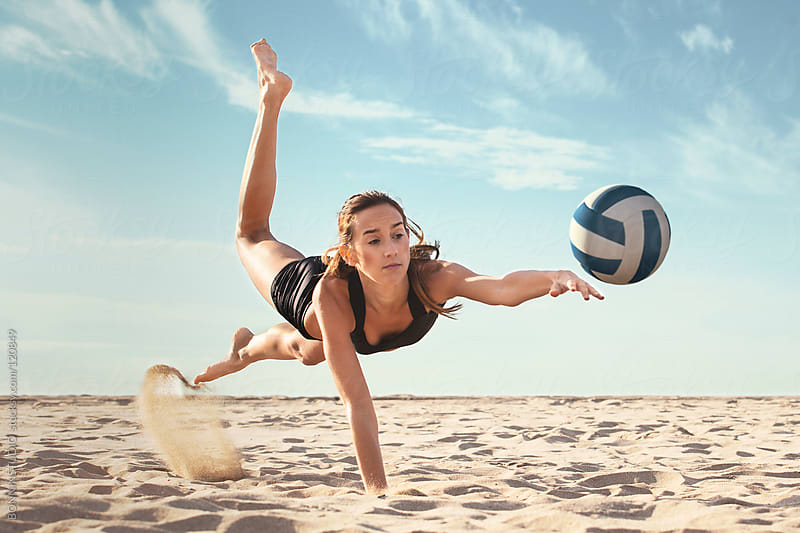 Beach volleyball. Sporty woman hitting a ball in a sunny day. by BONNINSTUDIO for Stocksy United