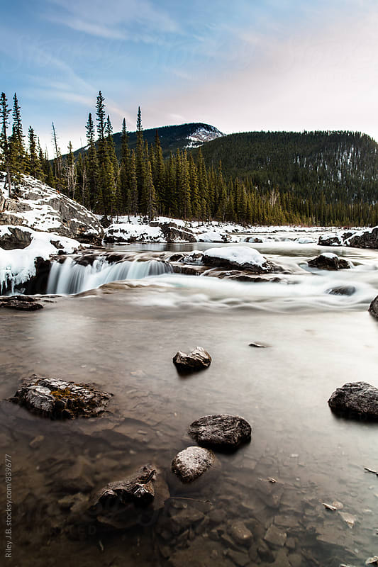 A river empties into a small waterfall. by Riley J.B. for Stocksy United