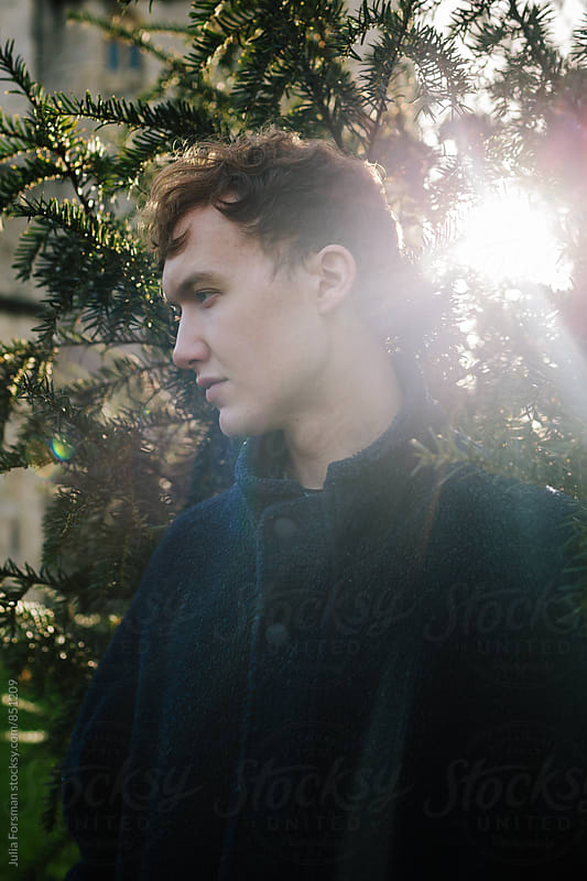 Beautiful young man with the sun streaming behind him. by Julia Forsman for Stocksy United