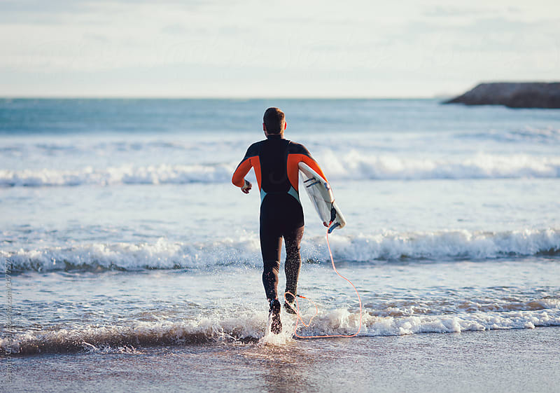 Surfer running about to get in the water by Leandro Crespi for Stocksy United