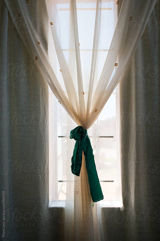 Close-up of beautifully decorated curtain with green bow by Trent Lanz for Stocksy United