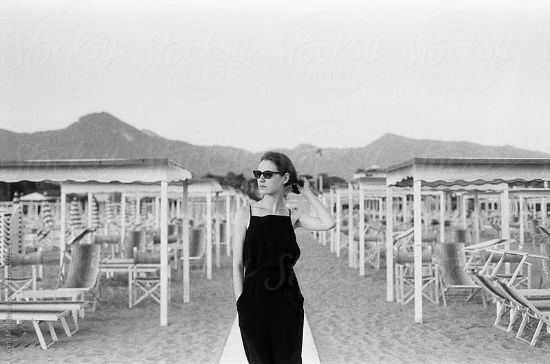 A film portrait of young beautiful woman standing on the beach by Anna Malgina for Stocksy United