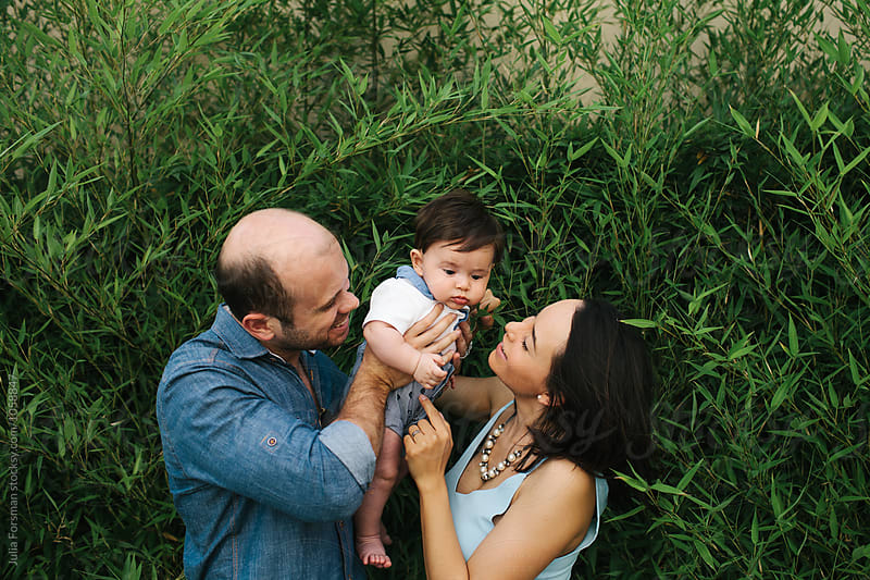 Mother and father fuss over their adorable child. by Julia Forsman for Stocksy United