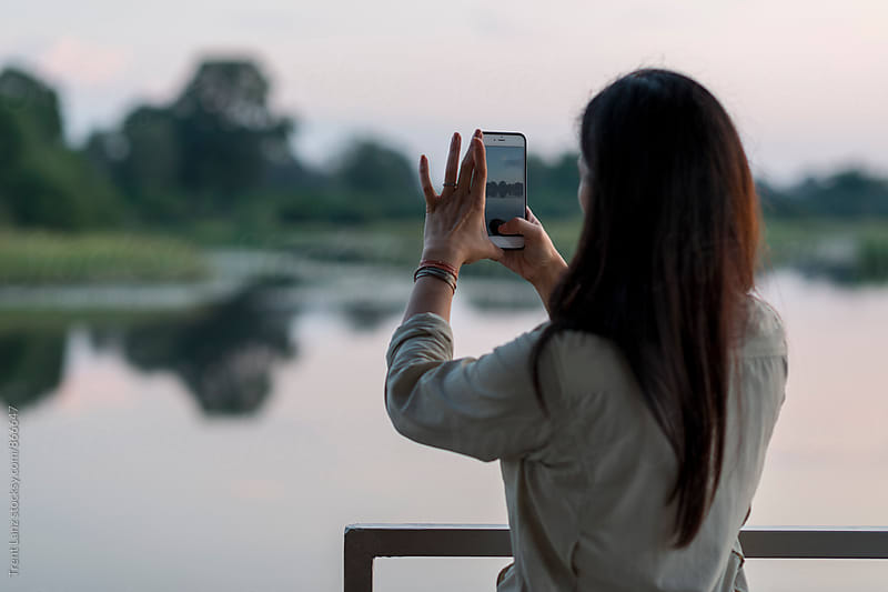 Back view of woman taking photo of riverscape on safari by Trent Lanz for Stocksy United