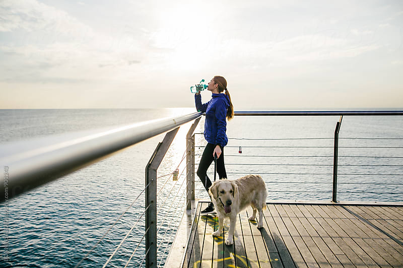 Woman with her dog drinking water after workout at sunrise. by BONNINSTUDIO for Stocksy United