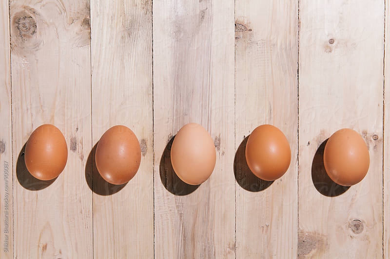 Eggs on a wooden background. by Shikhar Bhattarai for Stocksy United