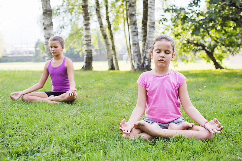 Two little girls doing yoga at the park by michela ravasio for Stocksy United