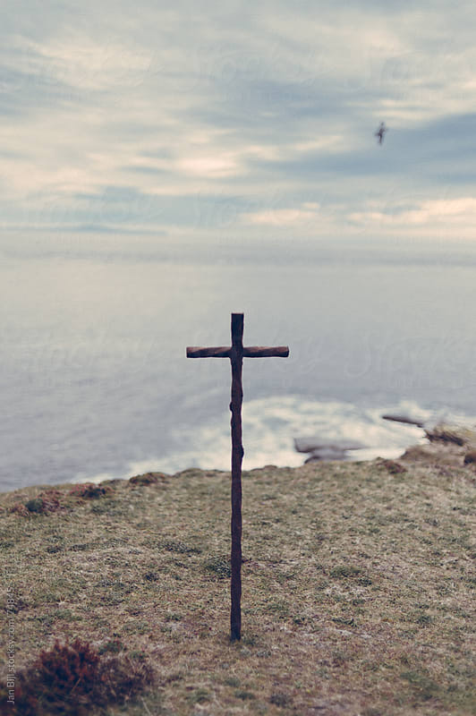Cross on a cliff  over looking the ocean in Hoy, orkney islands, scotland by Jan Bijl for Stocksy United