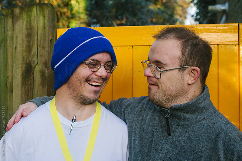 Two men with Down's Syndrome with their arms around each other share a joke. by Julia Forsman for Stocksy United