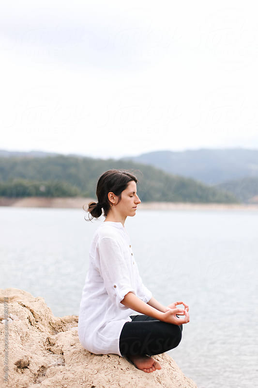 Woman meditating in front of a lake by Marija Kovac for Stocksy United