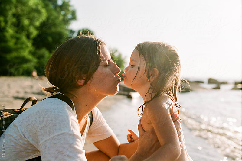 mother kisses daughter on beach by Maria Manco for Stocksy United