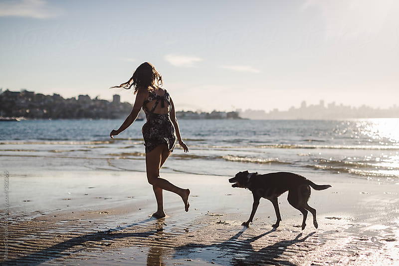 Woman playing with her dog on the beach by Mauro Grigollo for Stocksy United
