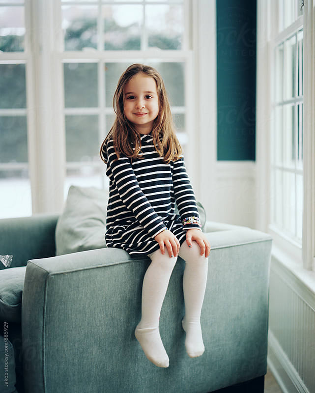 Beautiful young girl sitting on the arm of a chair by Jakob for Stocksy United