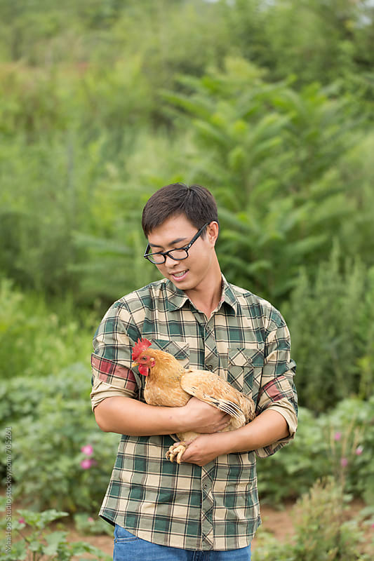 A young male farmer holding chicken by Maa Hoo for Stocksy United