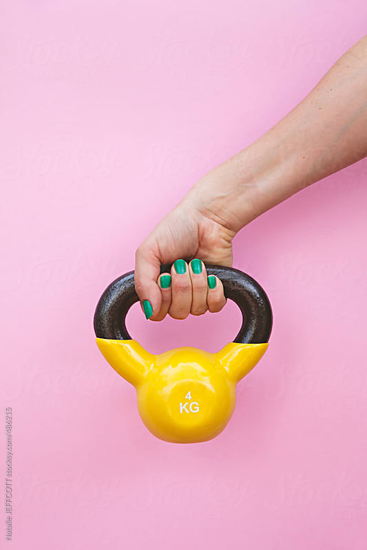 studio image of arm lifting colourful yellow kettle bell weight against a pink background by Natalie JEFFCOTT for Stocksy United