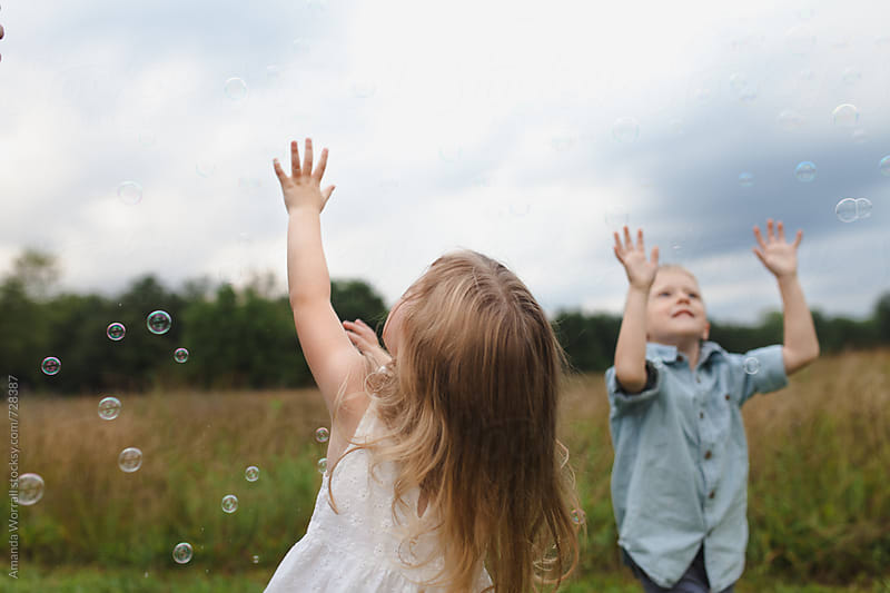 Boy and girl reaching toward the sky to pop bubbles by Amanda Worrall for Stocksy United