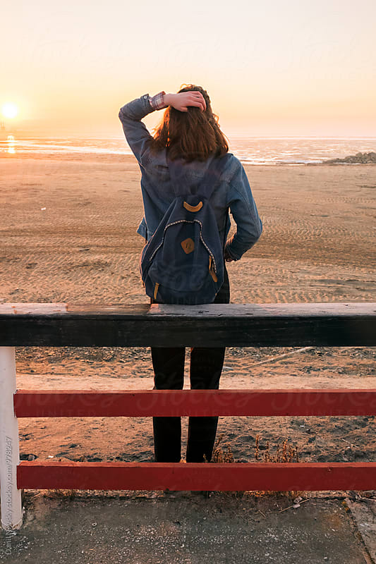 Back view of girl with backpack watching sunrise by Danil Nevsky for Stocksy United