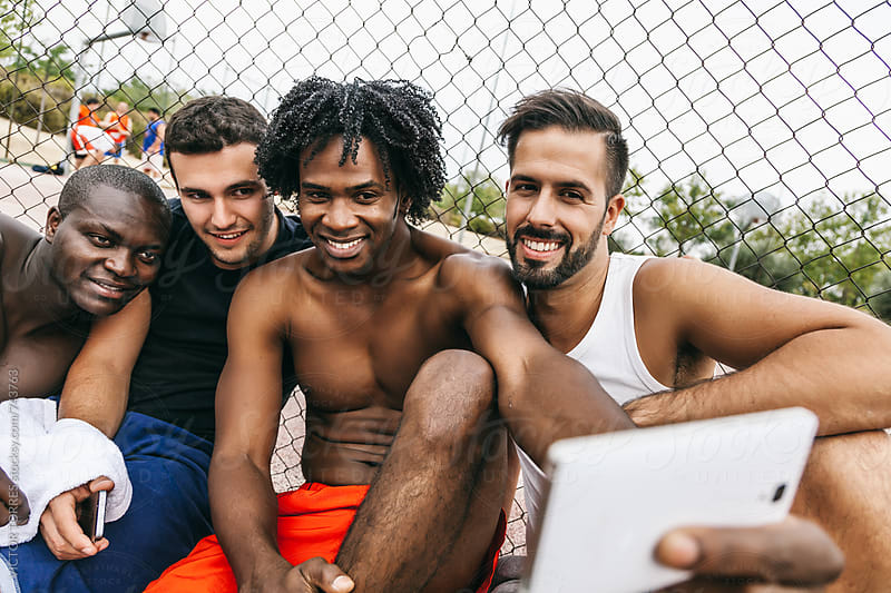 Friends Taking a Selfie During a Rest After a Street Basketball Game by VICTOR TORRES for Stocksy United