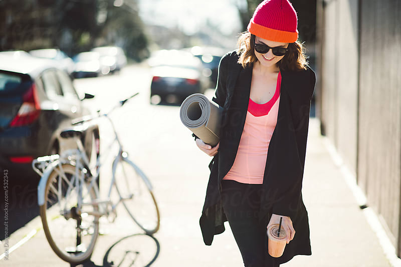 Young woman walking down city street after a yoga class by Kate Daigneault for Stocksy United
