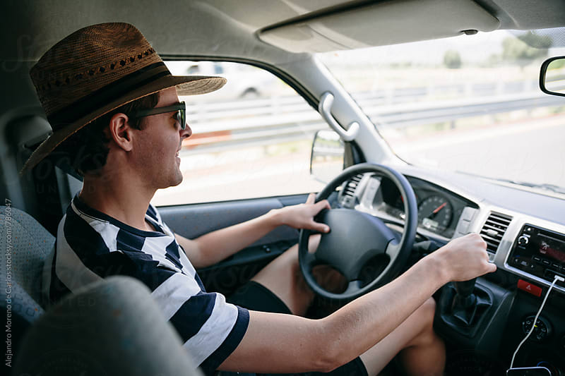 Young man with a straw hat and sunglasses driving a van on a highway by Alejandro Moreno de Carlos for Stocksy United