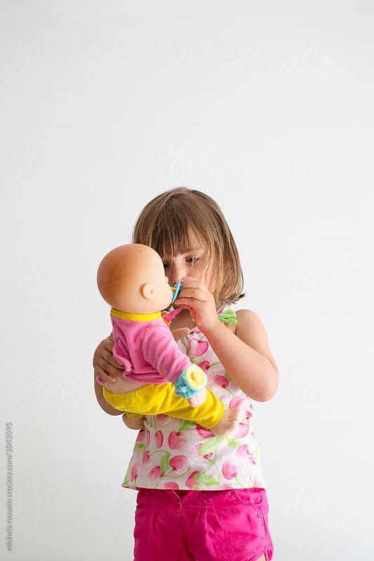 Baby girl takes care of her doll by michela ravasio for Stocksy United