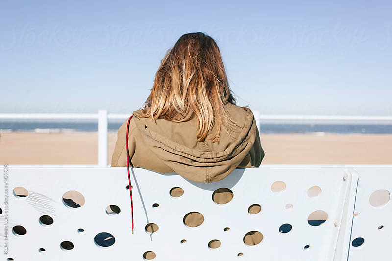 Girl sitting on a bench enjoying the view of the ocean. by Koen Meershoek for Stocksy United