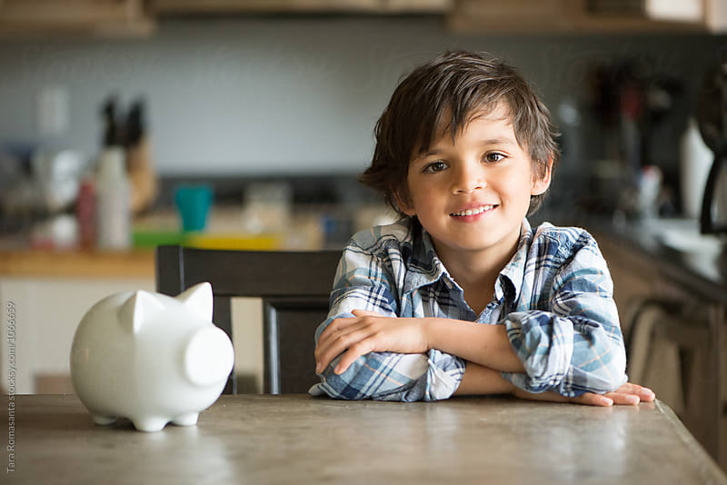 boy smiles after putting coins in his piggy bank by Tara Romasanta for Stocksy United