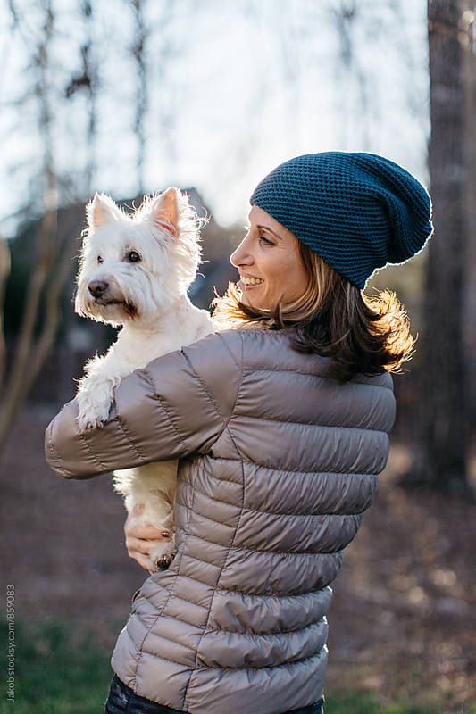 A beautiful woman holding a small white dog  by Jakob for Stocksy United