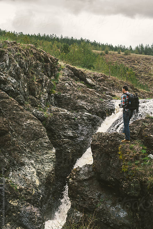 Man standing on the rock by the waterfall by Aleksandra Jankovic for Stocksy United