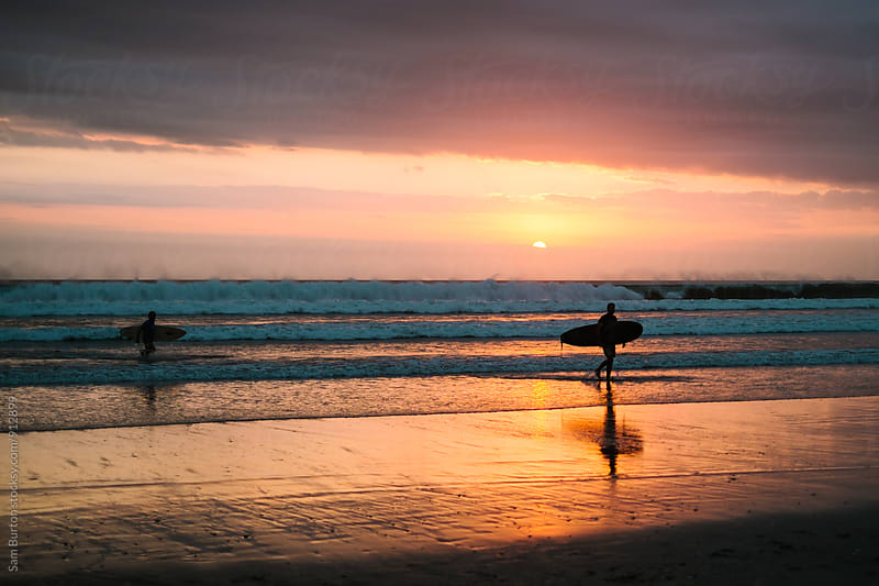 Surfers at sunset by Sam Burton for Stocksy United