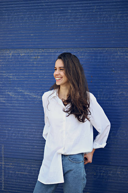 Girl in a white shirt smiling and standing in front of blue doors by Hamza Kulenović for Stocksy United