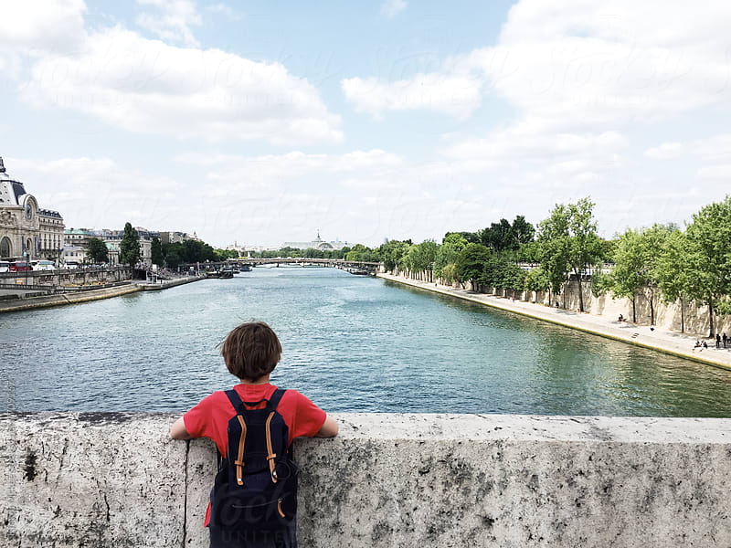 Boy looking out over bridge in Paris by Kirstin Mckee for Stocksy United