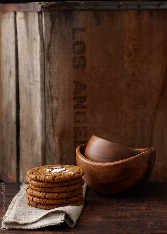 Stack of cookies and wood bowls in front of antique wood crate by Sherry Heck for Stocksy United