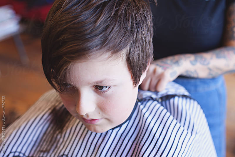 A young boy getting a hair cut at the barber by Natalie JEFFCOTT for Stocksy United