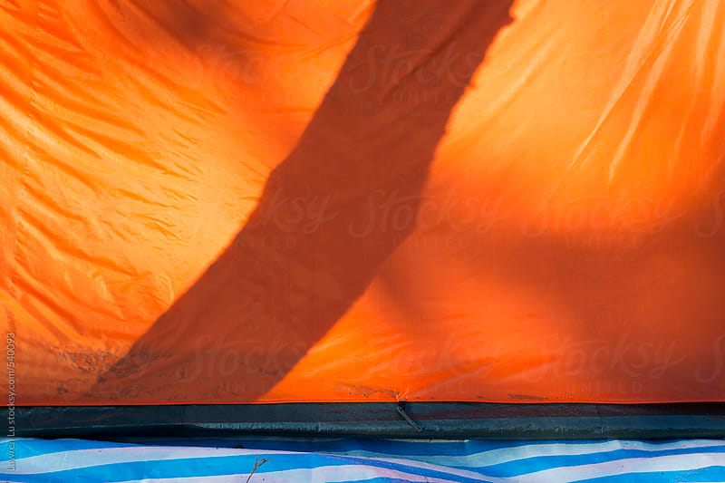 Shadow of branch on orange tent by Lawren Lu for Stocksy United