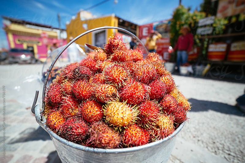 Metal bouquet full of fresh ramboutan fruits in the street in a local market by Alejandro Moreno de Carlos for Stocksy United